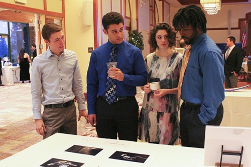From left to right, The Initiative's Kyle Tyson, Anothony Johnson, Raven Kauba, and Darius Upshaw discuss the artwork that is on display and for sale at the First Annual Phi Theta Kappa Fundraiser Banquet on Mar. 12, 2016.  (Photograph by Timon Barkley)