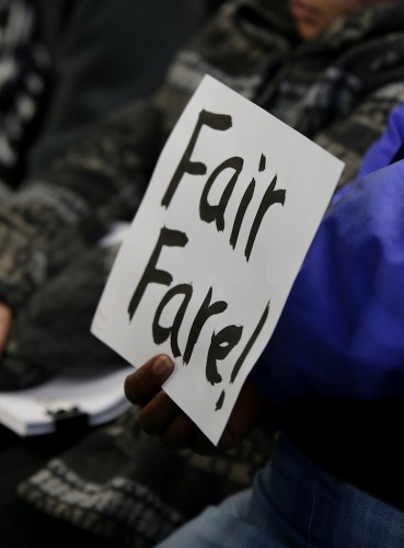 An audience member holds up a sign that reads 'Fair Fare!' during the Sacramento Regional Transit board meeting Monday. Several protesters attended the meeting. (Photo by Kyle Elsasser)