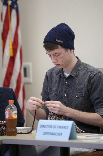 CAEB president Justin Nicholson knits during a student senate meeting on Feb. 25.  (Photo by Kyle Elsasser)