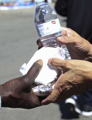 Local actor Sosa Hernandez hands food and bottled water to a local homeless man in downtown Sacramento, CA, around Loaves and Fishes on April 14, 2016. Hernandez uses his own income to purchase these supplies for the homeless community simply because he can and feels he should.