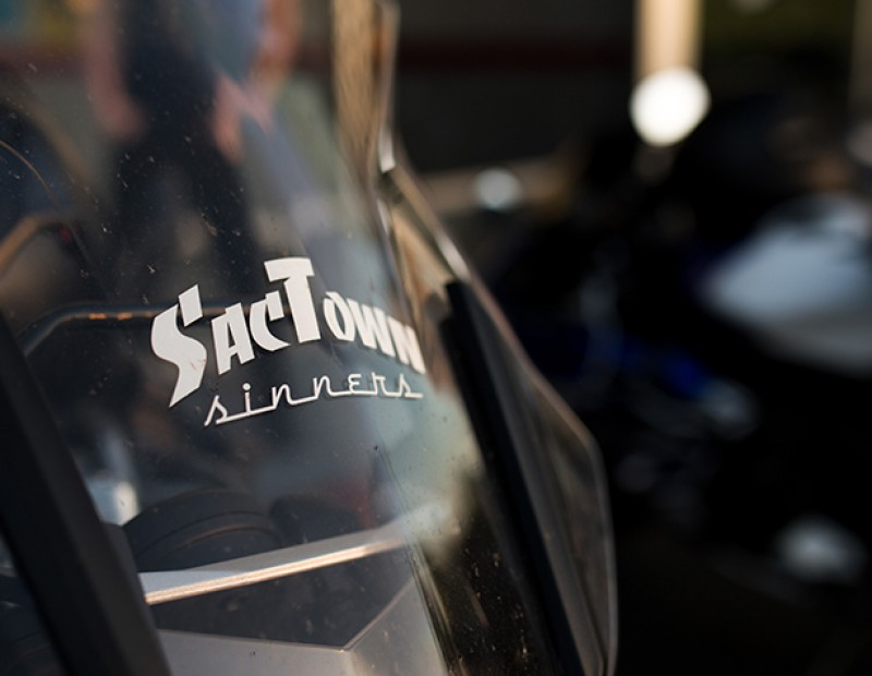 A decal of the SacTown Sinners logo located on Burak Kocal's BMW motorcycle. Kocal is a member of the Sactown Sinners, a motorcycle club featuring bikes from the Sacramento area. (Photo by Kyle Elsasser)