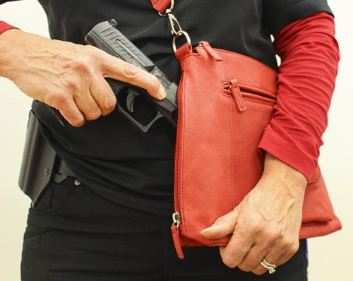 Debbie MacDonald poses with her gun and purse. MacDonald is the founder of the Well Armed Woman Sacramento chapter, which is an all woman's firearm group. (Photo by Hannah Darden)