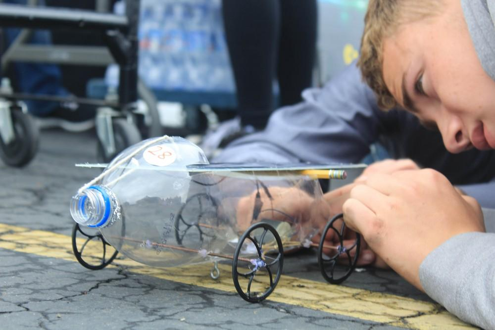 A high school student at puts the finishing touches on his solar car at SMUD solar  car competition on May 6.