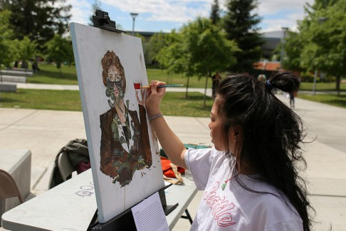 American River College student Kashia Lynhiavue paints one of her works titled
