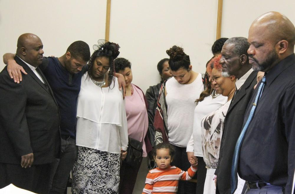 Faith Covenant Community Church's pastor Kendall Young prays with members of the congregation while embracing one another. The church meets every Sunday at ARC in Raef Hall. (Photo by Timon Barkley)