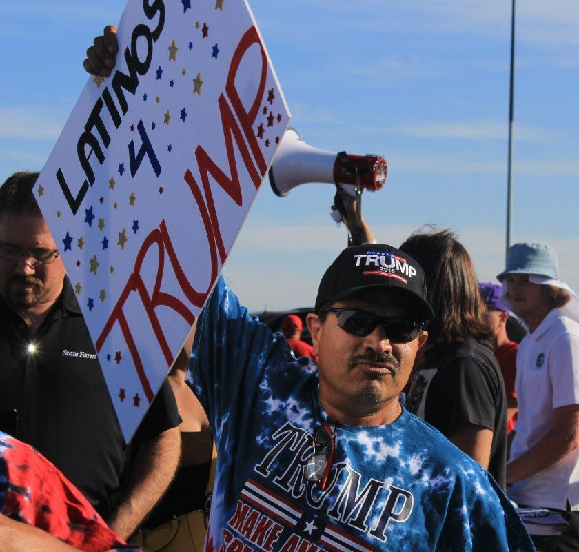 "A Donald Trump supporter holds up a sign reading ""Latinos 4 Trump"" in line to hear the presidential hopeful speak. (Photo by Jordan Schauberger)"