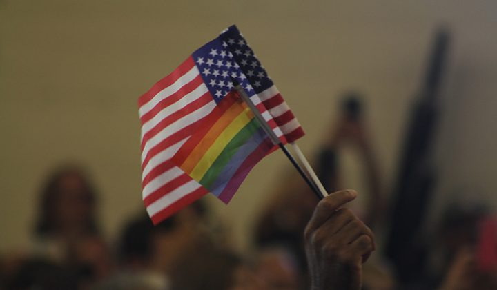 A supporter of Hillary Clinton waves an American flag and a rainbow LGBT flag in unison at a rally event at Sacramento City College on June 5, 2016. (Photo by Mack Ervin III)
