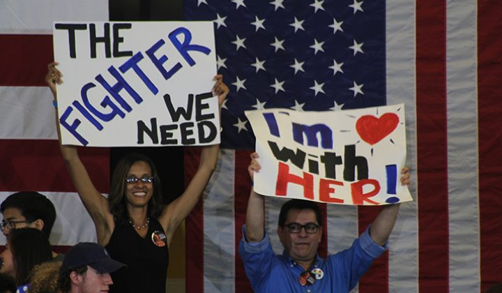 Two supporters of democratic front runner Hillary Clinton hold up signs in support of Clinton at a campaign event at Sacramento City College on June 5, 2016. The supporters stood behind Clinton as she spoke to her supporters. (Photo by Mack Ervin III)