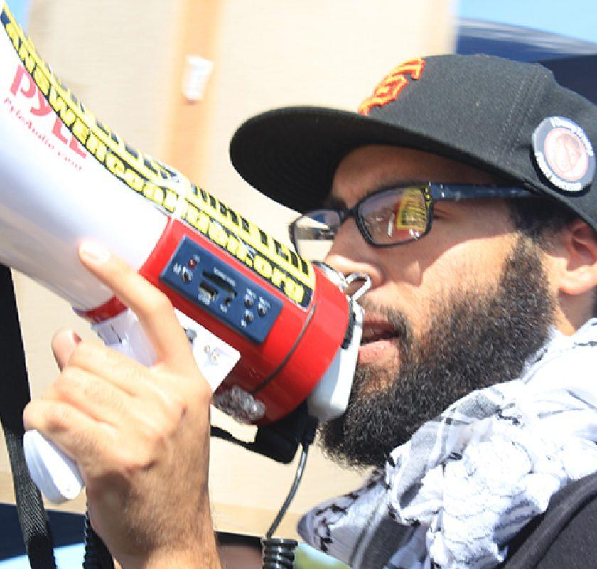 "Jamier Sale chants ""no more hate"" through a megaphone in protest of  Donald J. Trump at his rally in Sacramento on June 1, 2016. A group of about 50 protesters where at the rally whom marched around the parking lot before Trump's speech. (Photo by Robert Hansen)"
