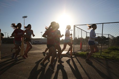 The American River College women's cross country team warm up in the parking lot behind the new soccer stadium before their first meet of the season at Sierra College on Sep. 2. (Photo by Cheyenne Drury)