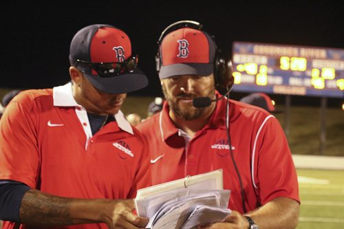 American River College wide recievers coach Michael Johnson and head coach Jon Osterhout look over the playbook on the sidelines during a game against Modesto Junior College on Sept. 10 at Cosumnes River College. ARC won 47-33. (Photo by Laodicea Broadway)