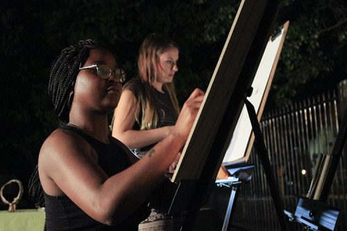American River College Art Club members Aerial Sudds (left) and Brianna Hulce (right) work on paintings at the live art show and open mic night at Oak Park Brewing Company in Sacramento, California on Sept. 6, 2016. The art club attended the event to make and sell art in the community. (Photo by Hannah Darden)