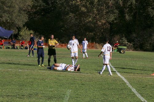 Hartnell College midfielder Patricio Nolasco lies on the field while other players talk with the referee during a soccer game against American River College on Sept. 20. ARC lost 4-0. (Photo by John Ennis)