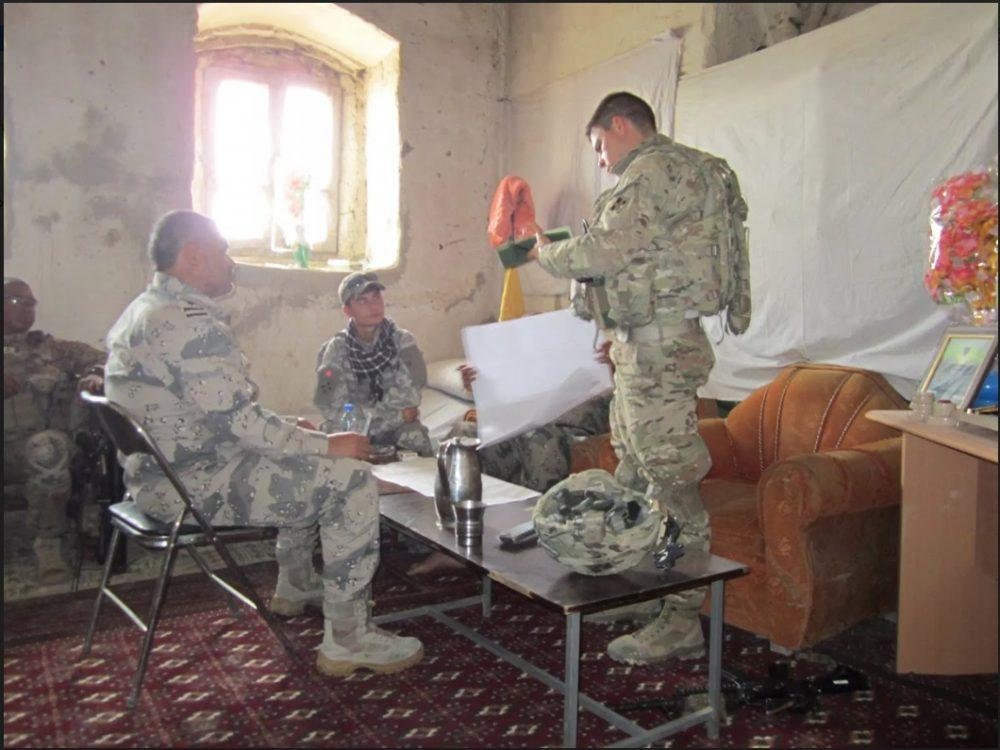 Qais Ahmad (center) translates for first lieutenant Noah Christen (right) from 4th ID troops and Colonel shams kareemi, Commander of Afghan border police (left) in Khogyani district of Nangarhar province. (courtesy of Qais Ahmad)