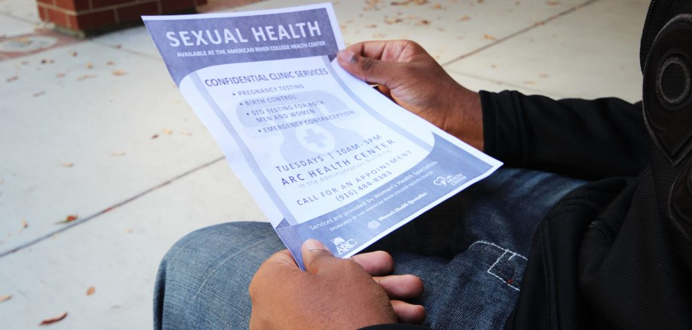 ARC+student+looks+at+the+flyer+for+the+Sexual+Health+Clinic.+%28Photo+by+Cheyenne+Drury%29