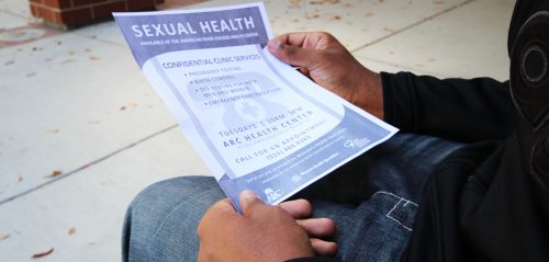 ARC student looks at the flyer for the Sexual Health Clinic. (Photo by Cheyenne Drury)