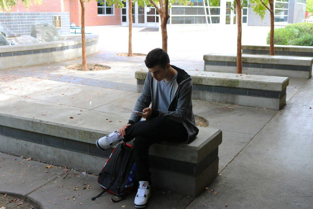 ARC student Jack Simmons using his smartphone next to the Liberal Arts breezeway, October 13, 2016.