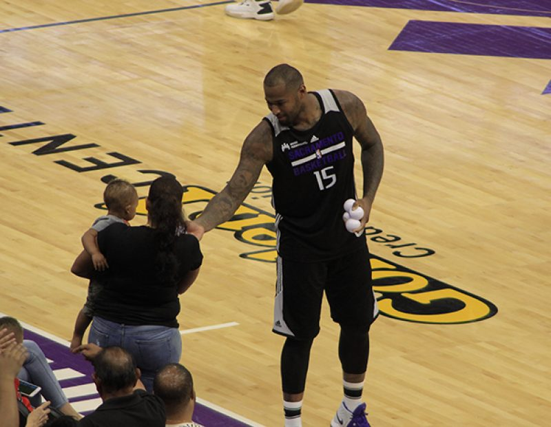 "DeMarcus Cousins handing a King's shirt to a mother and baby during ""Fan Fest"" at the Golden 1 Center on Oct. 1. (Photo by Luis Gael Jimenez)"