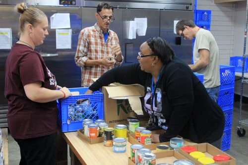 ARC student Peral Calhoun (front right) helps unload canned foods at the Carmichael Seventh-day Adventist Church food pantry, ahead of the holiday season rush. (Photo by Jordan Shcauberger)