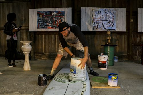 Artist John Klaiber paints the flower of life geometric design on an old surfboard during his
