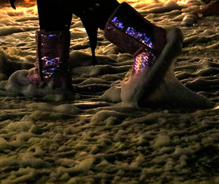 "A girl walks through foam, meant to look like snow, in sparkly boots at ""Global Winter Wonderland"" at Cal Expo on Sunday in Sacramento, Calif. (Photo by Cheyenne Drury)"