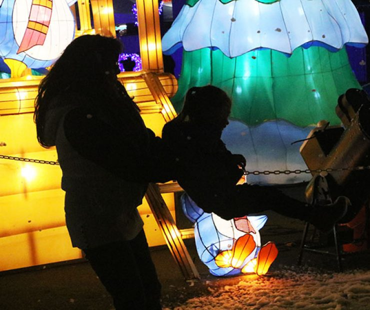 "A woman swings around a child in the falling foam, meant to look like snow, at ""Global Winter Wonderland"" at Cal Expo in on Sunday in Sacramento, Calif. (Photo by Cheyenne Drury)"