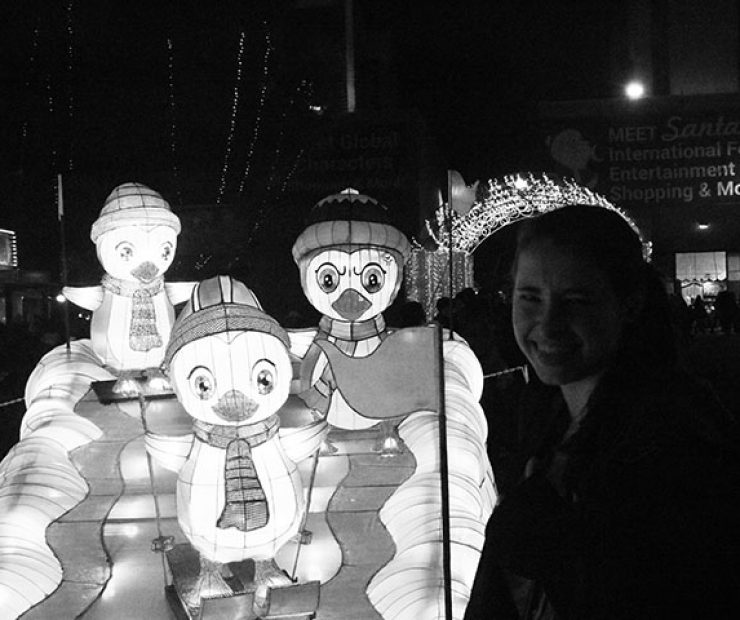 "ARC student Shelley Sauter poses with a lit up display of penguins at ""Global Winter Wonderland"" at Cal Expo on Sunday in Sacramento, Calif. (Photo by Cheyenne Drury)"