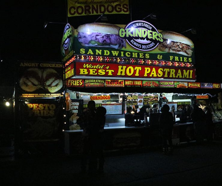"People stand in front of and order food from ""World's Best Hot Pastrami"" at ""Global Winter Wonderland"" at Cal Expo on Sunday in Sacramento, Calif. (Photo By Cheyenne Drury)"