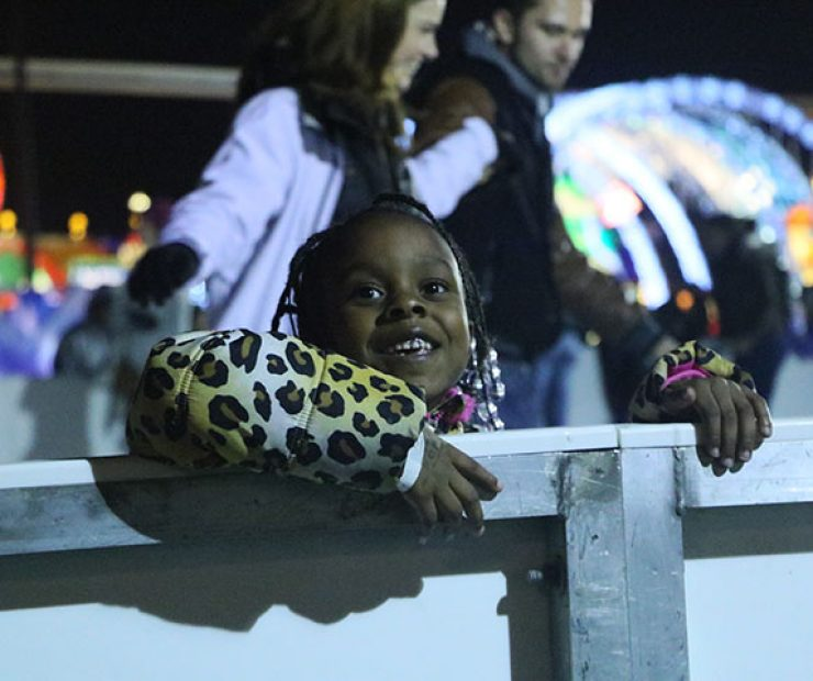 "A girl smiles as she hold onto the wall for support as she ice skates at ""Global Winter Wonderland"" at Cal Expo on Sunday in Sacramento, Calif. (Photo by Cheyenne Drury)"