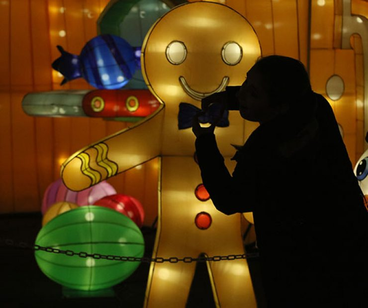 "ARC student Shelley Sauter pretends to adjust the bow on a lit up gingerbread man at ""Global Winter Wonderland"" at Cal Expo on Sunday in Sacramento, Calif. (Photo by Cheyenne Drury)"
