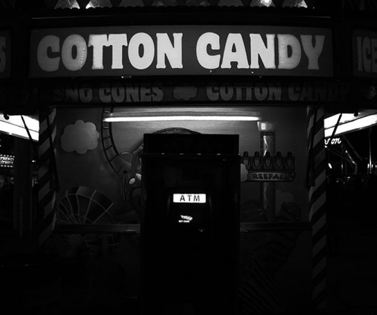 "An ATM machine beneath a sign for cotton candy at ""Global Winter Wonderland"" at Cal Expo on Sunday in Sacramento, Calif. (Photo by Cheyenne Drury)"