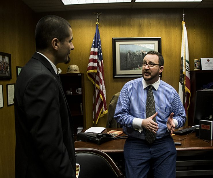 Student Senator Julian Lopez gives Assemblymember Devon J. Mathis his elevator pitch for mental health awareness. Mathis saw that the student senators were being followed around by a photographer and decided to give them a chance to sell him on their idea. (Photo by Luis Gael Jimenez)