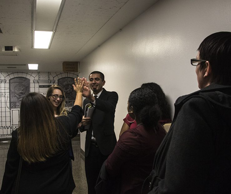 Julian Lopez and Ashley Hayes-Stone inform the rest of the student senators of their impromptu meeting with Assemblymember Devon J. Mathis. The group exchanges high fives. (Photo by Luis Gael Jimenez)