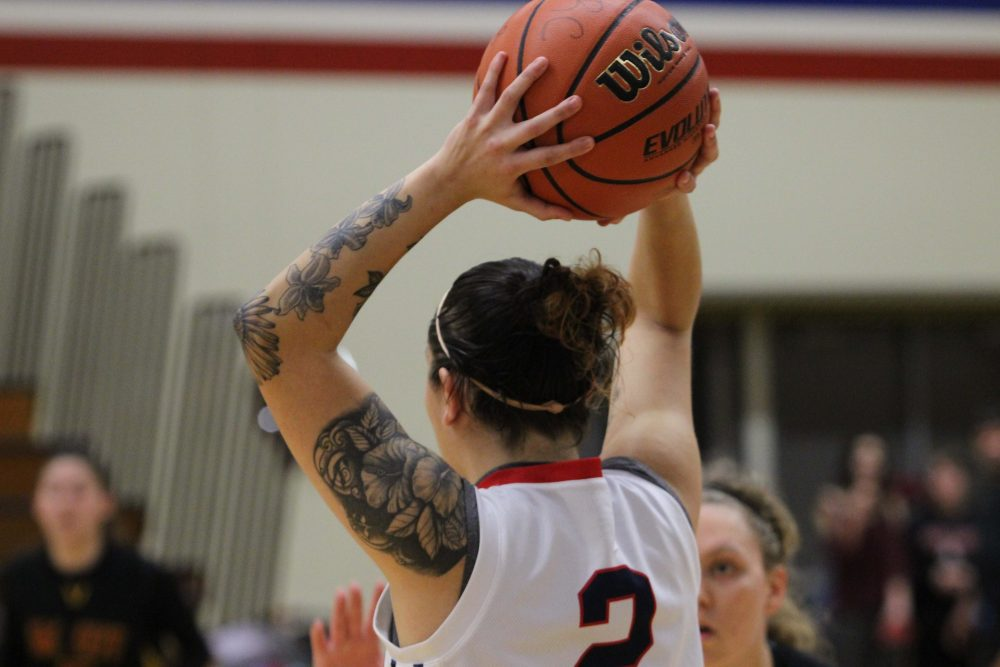 ARC guard position Rauline Martinez holds the ball over her head to pass to a teamate. (photo gallery by Lidiya Grib)