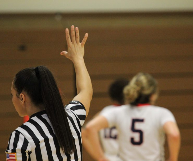 Referee for the ARC and SCC women's basketball game holds her hand up to signal during the game. (photo gallery by Lidiya Grib)