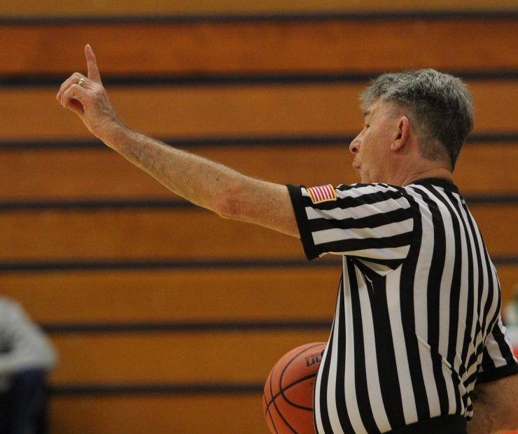 Referee for the ARC and SCC women's basketball game signals during the game.