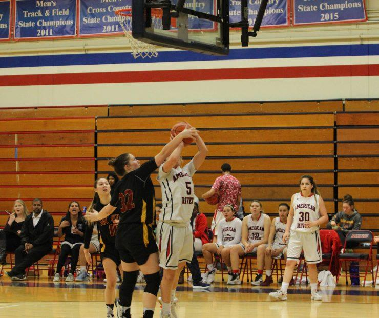 ARC guard position, Jennifer Manduca jumps to to shoot as Sac. City College forward Meghan Case blocks the shot. (photo gallery by Lidiya Grib)