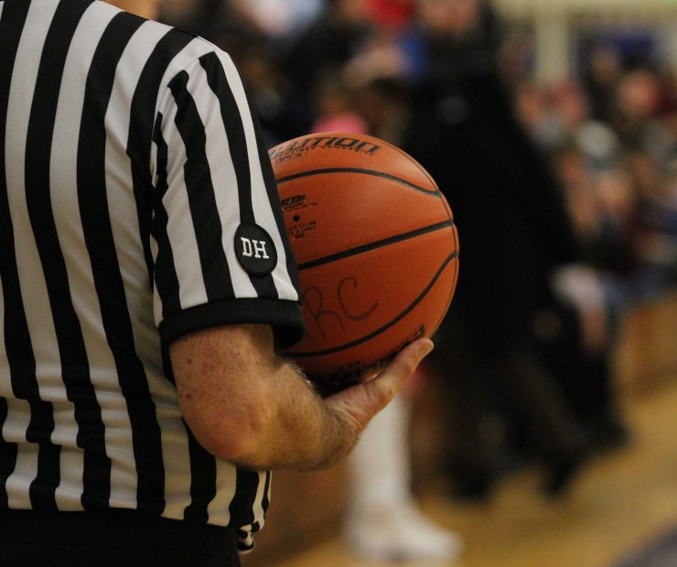Referee for the ARC and SCC women's basketball game holds the ball. (photo gallery by Lidiya Grib)