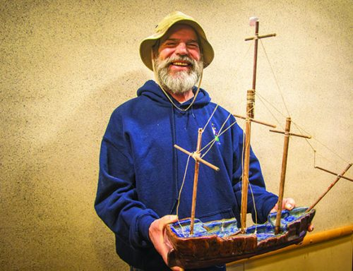 Tom Roberts holds up a ceramic boat that he made at American River College. Roberts survived a traumatic brain injury in 1978. He has been enrolled at ARC every semester since 1989. He passed away on Oct. 22, 2016 of cancer. (Photo by Luis Gael Jimenez)