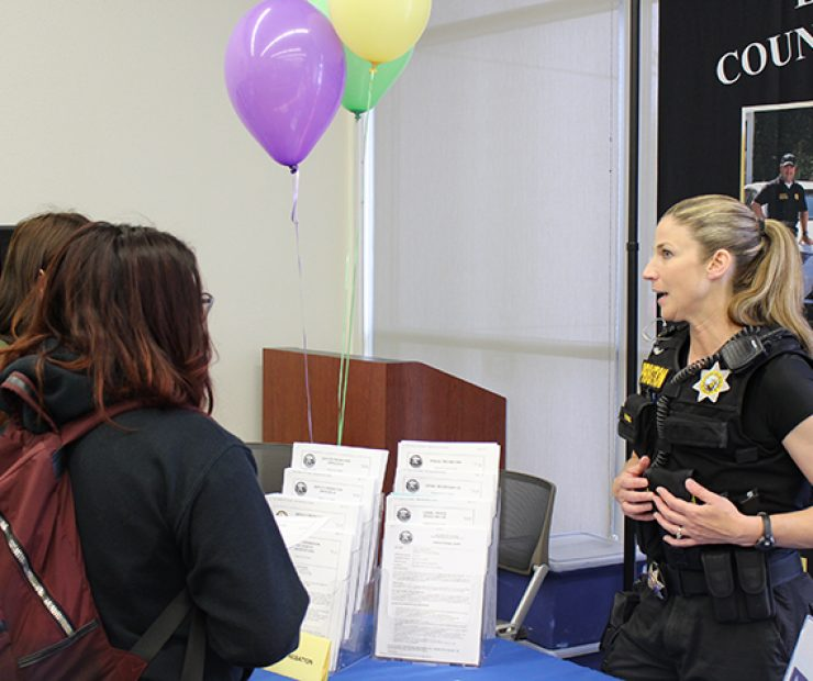 An El Dorado County police officer offers her knowledge to two students.
