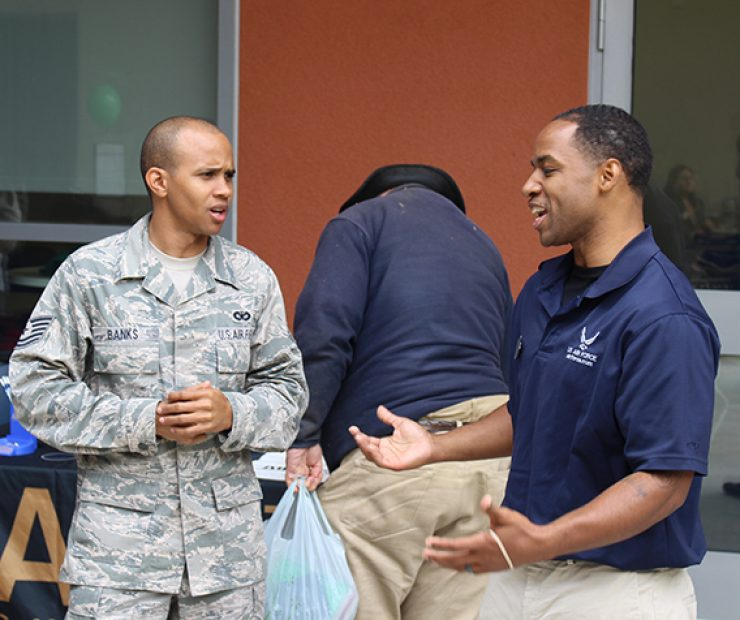Two veterans of the United States Air Force have a conversation at the ARC Career Fair.