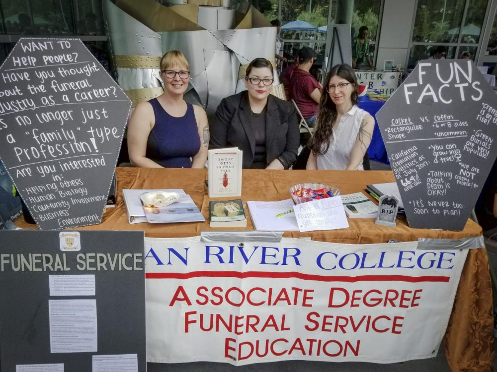 "Members of the Funeral Services Department at American River College sit at a booth for ""Welcome Day,"" on Sept. 7, 2017. (Photo by Hannah Yates)"