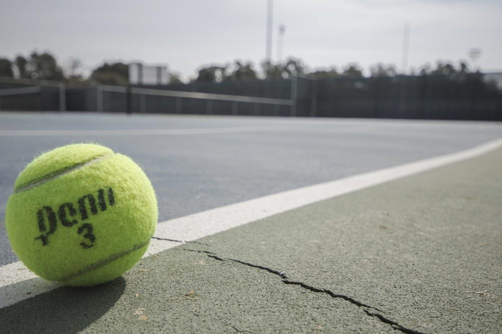 A tennis ball sits on the cracked ground of the American River College tennis courts. The courts are so badly cracked that many of them are unusable. (Photo by Brienna Edwards)