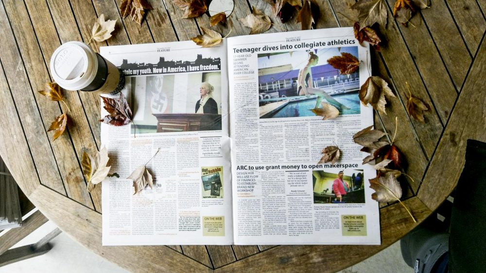 The Current newspaper lays on a table surrounded by fall leaves and a cup of coffee. (photo illustration by Brienna Edwards)