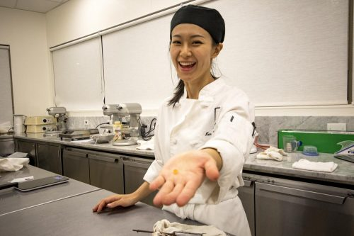Head chef Lisa Lam Chiao holds a piece of candied orange peel as she prepares to make orange hazlenut chocolate bark. Chiao prepared the orange slices in her own home the night before. (Photo by Ashley Hayes-Stone)
