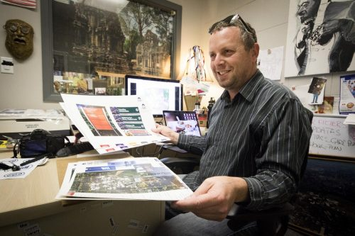 American River College Printing Services Supervisor Don Reid holds up a prototype for the new campus maps that he is working on. (Photo by Ashley Hayes-Stone)