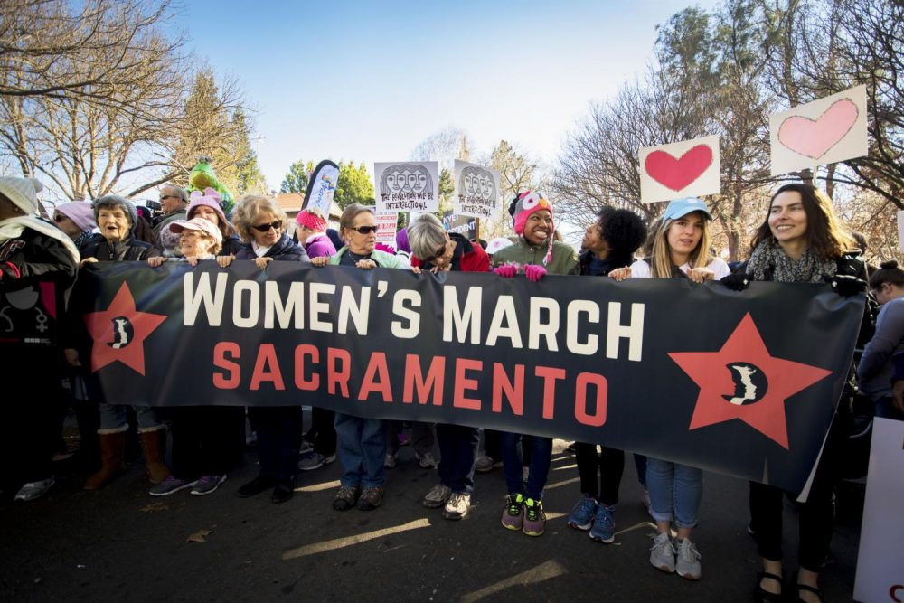 A+group+of+protesters+hold+up+a+%22Women%27s+March+Sacramento%22+sign+during+the+annual+Sacramento+Women%27s+March+on+Jan.+20%2C+2018+in+Sacramento%2C+California.++%28Photo+by+Ashley+Hayes-Stone%29
