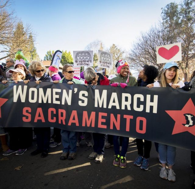 "A group of protesters hold up a ""Women's March Sacramento"" sign during the annual Sacramento Women's March on Jan. 20, 2018 in Sacramento, California."