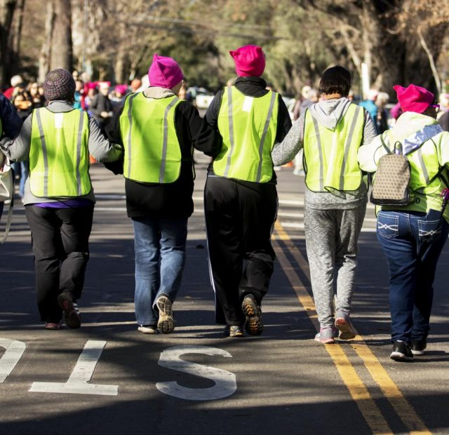 The Women's March volunteers link arms as they help lead the march to the California State Capitol on Jan. 20 in Sacramento, California.