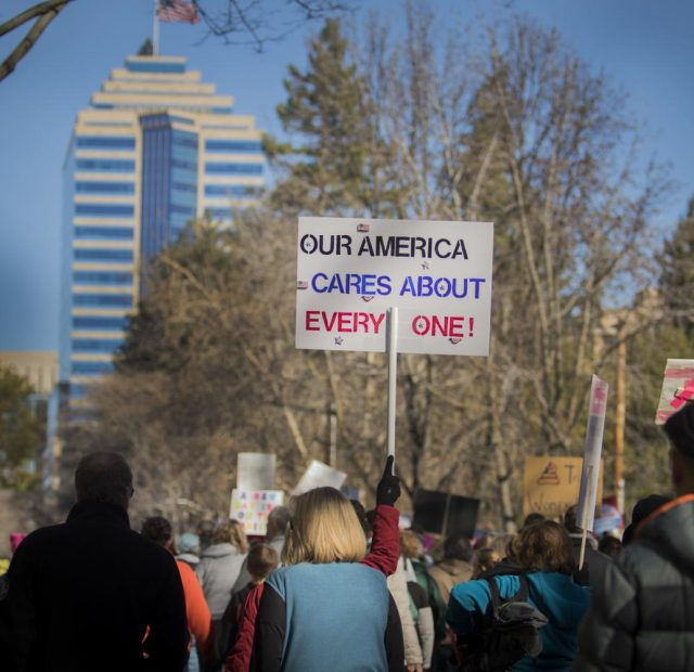 "A protester holds up a ""Our American cares about everyone"" sign during the march to the California State Capitol to support women's rights on Jan. 20, 2018 in Sacramento, California."